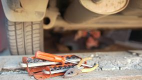 Set of tools in front of man underneath a car unscrewing details from under tray. De-focused stock footage