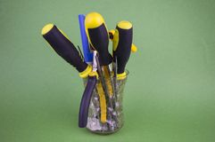 A set of tools in the glass - screwdrivers, pliers, nibs, yellow-black natfelas on a green background, there is an empty space to royalty free stock photos