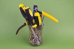 A set of tools in the glass - screwdrivers, pliers, nibs, yellow-black natfelas on a green background, there is an empty space to stock photography