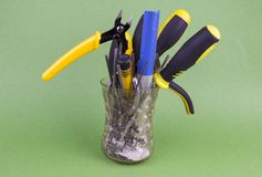 A set of tools in the glass - screwdrivers, pliers, nibs, yellow-black natfelas on a green background, there is an empty space to stock image