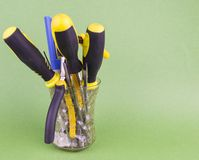A set of tools in the glass - screwdrivers, pliers, nibs, yellow-black natfelas on a green background, there is an empty space to stock photos