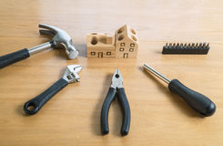 Set of tools and handmade wood house toy. Stock Photos