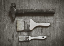 Set of tools: a large brush to paint a small brush to paint and old hammer nails on wooden background. Abstraction of hard work royalty free stock images