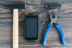 Set of tools and shockproof phone. On wooden background Stock Images