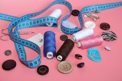 A set of tools for the tailor - thread, scissors, pins, coils, needles, measuring meter. On a pink background. Flatlay stock images