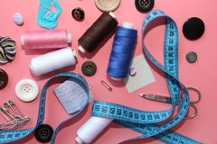 A set of tools for the tailor - thread, scissors, pins, coils, needles, measuring meter. On a pink background. Flatlay royalty free stock photos