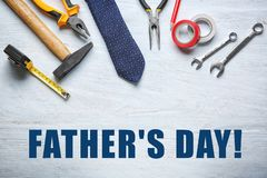 Set of tools with tie on light wooden background. Father's Day celebration royalty free stock photo