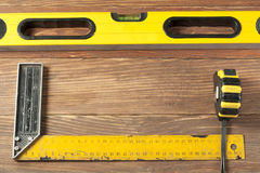 Set of tools at wooden table. meter measuring line construction level and square ruler maintenance concept