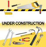 Set of tools with words under construction. Saw, tape measure, wrench, spanner, paint roll, hammer, cutter, pliers. Stock Photos