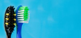 Set of toothbrushes in glass on blue background. Concept toothbrush selection, copy space.  stock images