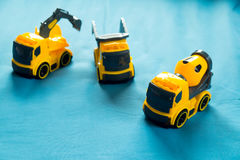Set of toy Industrial Vehicle. Three yellow toy  Industrial Vehicle on blue bed, Children`s construction machinery Royalty Free Stock Images