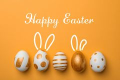 Set of traditional Easter eggs decorated with golden paint on color background, top view. Space for text stock photo