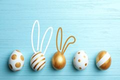 Set of traditional Easter eggs decorated with golden paint on wooden background, top view. stock images