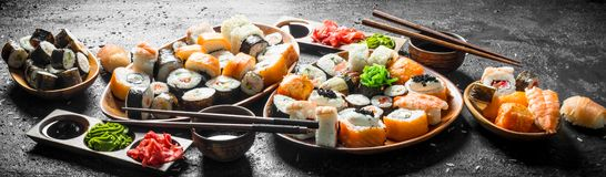 Set of traditional Japanese food sushi with soy sauce and ginger. On black rustic background royalty free stock photography