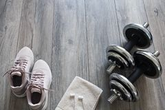Set for training: dumbbells, sneakers, headphones. Dumbbells on a wooden floor royalty free stock photo