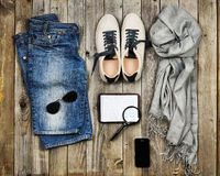 Set of travel items. Top aerial view. Set of travel items including scarf, sunglasses, sneakers, note book, magnifying glass, mobile phone and jeans. Planning Stock Images