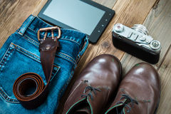 Set for the traveler with a digitizer, rangefinder camera, blue. Traveler set with a digitizer, rangefinder camera,  leather belt, blue jeans and brown boots Royalty Free Stock Image