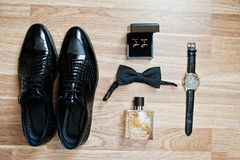 Set of trendy men`s clothes and accesories. Set groom bow ties,. Shoes, cufflinks, watches and perfume on wooden background Stock Images