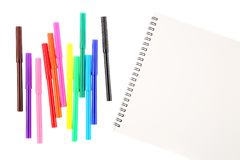 Set of twelve felt tip markers in different colors and a blank sketchbook with a space for text. Isolated on white background. Art. And creativity concept stock image