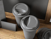Set of two black coffee cups, blank business cards and chalkboard on bookshelf. 3d render Royalty Free Stock Images