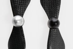 Set of two carbon fiber self-tightening propellers for a quadcop. Close up of set of two carbon fiber self-tightening propellers for a quadcopter drone on white Stock Photo