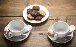 Set of two ceramic tea mugs with tea bags and plates of cookies.Preparation for brewing tea. Stock Image