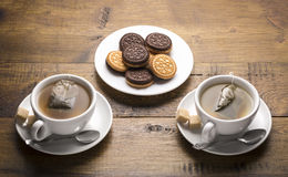 Set of two ceramic tea mugs with tea bags and plates of cookies.Serving and brewing tea. Royalty Free Stock Image