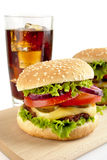 Set of two cheeseburgers and glass of cola on wooden board Stock Photography