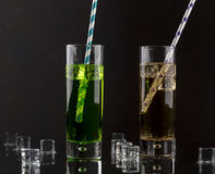 Set from two a collins glass with soda and colored straws. Royalty Free Stock Images