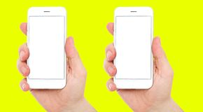 Set two different phones with blank display on yellow background, male hands hold phones.  royalty free stock photo