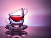 A set of 2 glass cups for tea on a purple and lilac background. Concept stock photography