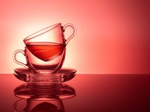 A set of two glass cups for tea on a red pink background stock photos