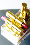 Set of two lipsticks. In red and fuchsia color in golden covers royalty free stock photos