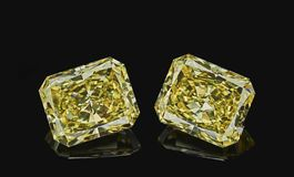 Set of two luxury yellow transparent sparkling gemstones emerald cut shape diamonds isolated on black background royalty free stock photos
