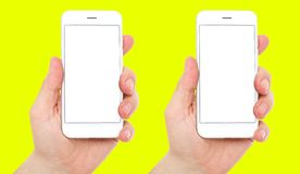 Set two phones with empty blank display isolated on yellow background, male hands hold phones vertical, 2 smart phones.  royalty free stock photos