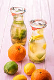 Set of two summer lemonade with ice and fruit like lemon, lime and mint leaves, summer drink with soda on pink background Royalty Free Stock Photography