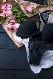 A set of underwear as a gift. Black lace. An intimate surprise on Valentine`s Day. Bouquet of pink roses. Free space for text or. Postcards Royalty Free Stock Photos