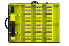 Set of universal screw-drivers. Replaceable tips of screw-drivers and the holder in a yellow box. Isolated on white royalty free stock photos