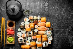 Set a variety of rolls, sushi and maki with green tea. On dark rustic background royalty free stock photo