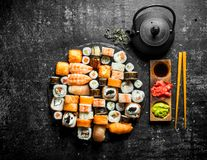 Set a variety of rolls, sushi and maki with green tea. On dark rustic background royalty free stock photography