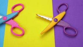 Minimal background with moving colorful wavy blade scissors.
