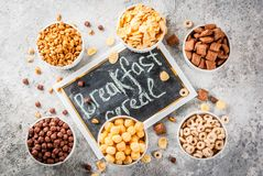 Various breakfast cereal. Set of various breakfast cereal corn flakes, puffs, pops, grey stone table copy space top view royalty free stock photo