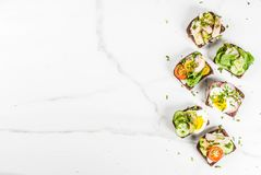 Set of various danish open sandwiches Smorrebrod with fish, egg. And fresh vegetables, white marble background copy space top view Royalty Free Stock Images
