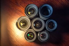 Set of various DSLR lenses with colorful reflections on wooden table. Set of various DSLR lenses with colorful reflections - shot from above on wooden background vector illustration