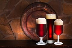 Set of various glasses of beer in cellar, pub or restaurant. Beer glasses, old beer barrel and brick wall on background. Royalty Free Stock Photography
