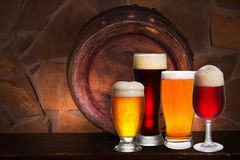 Set of various glasses of beer in cellar, pub or restaurant. Beer glasses, old beer barrel and brick wall on background. Royalty Free Stock Photos