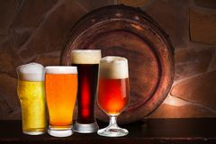 Set of various glasses of beer in cellar, pub or restaurant. Beer glasses, old beer barrel and brick wall on background. Stock Photo