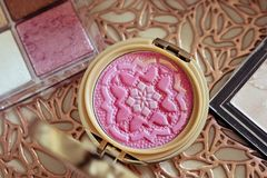 Top view of female`s make up set with pink blush palette and powder box on the beautiful golden background. stock photo