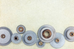 Set of various metal gearwheels on scratched brass surface Stock Images