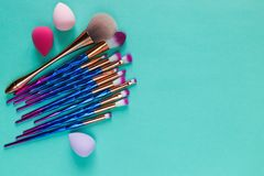 Set of various professional trendy fashion violet purple metallic makeup brushes, beauty blenders on pastel green background. royalty free stock photography